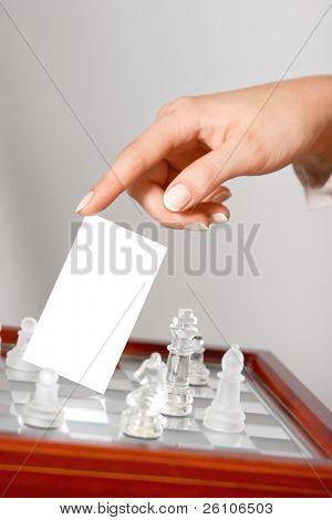 Woman hand holding blank business card  (visit card) over a chessboard with glass figures. Closeup.
