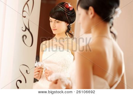 Slim beautiful woman with good hair dress, wearing luxurious wedding dress standing opposite to a mirror.