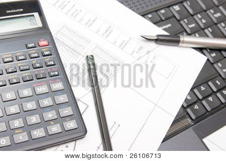 Calculator with fountain pen and pencil and house plan on the notebook. Closeup.