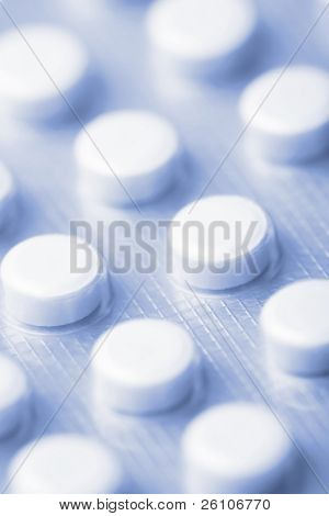 Closeup shot of a pack of pills. Toned in blue.
