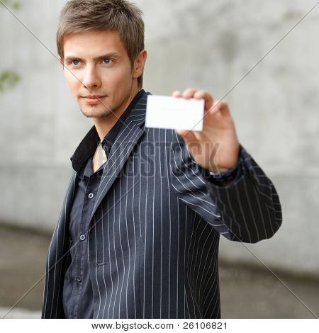 Portrait shot of young businessman showing blank business card. Focus on man. Outdoor.