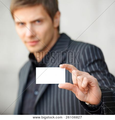Closeup portrait shot of young businessman showing blank business card. Focus on card. Outdoor.