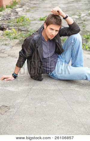 Portrait shot of a young attractive man sits on asphalt road, he is thinking. Outdoor.