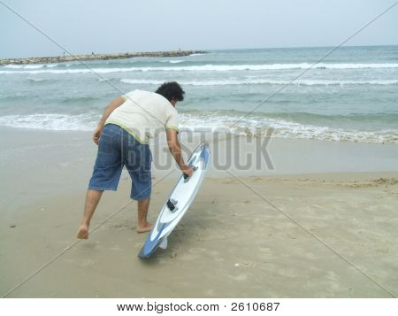 A Man Holding His Surfboard