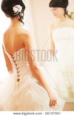Wedding shot of a slim beautiful woman wearing luxurious wedding dress standing opposite to a mirror.