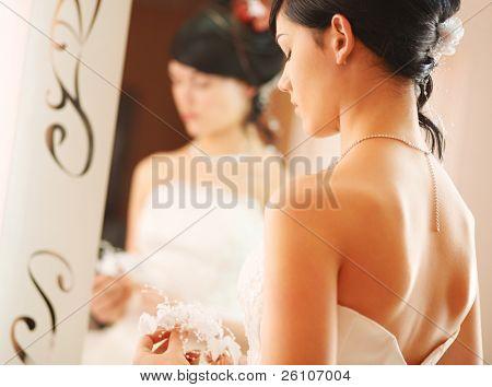 Closeup wedding shot of a slim beautiful woman wearing luxurious wedding dress standing opposite to a mirror.