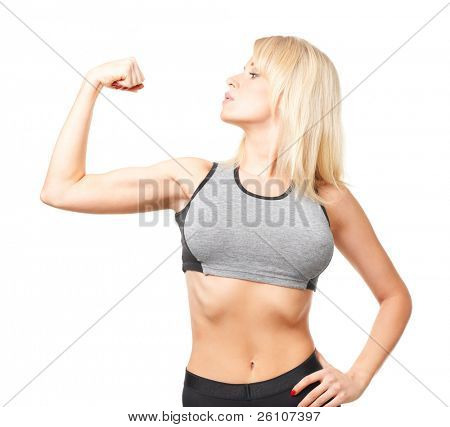 Studio shot of young happy woman in sports wear showing her biceps. Isolated on white.