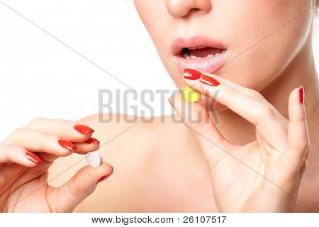 Young woman choosing to take between two pills. Isolated on white. Closeup.