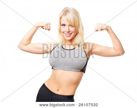 Studio shot of young happy smiling woman in sports wear showing her biceps. Isolated on white.