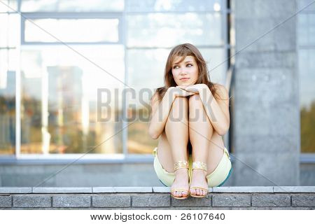 Sad cute student teenage girl sitting at urban scene, she put her head on her hands.