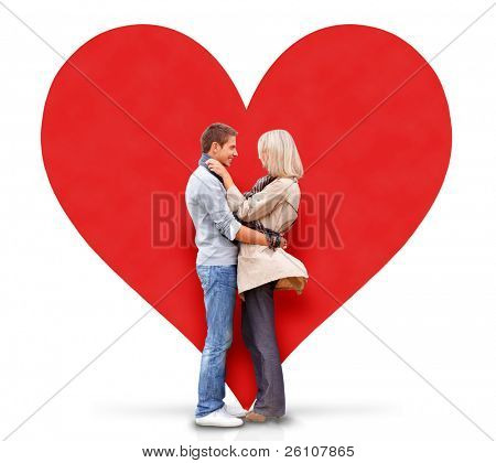 Young couple embracing, there is a big red heart behind them. Isolated on white background.