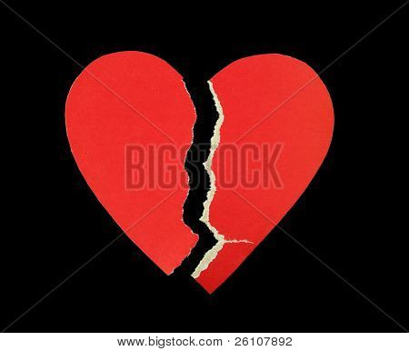 Broken red paper heart isolated on black background.