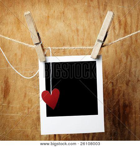 Leere Foto und kleine rote Papier Herz an die Wäscheleine hängen. Auf dunklen Grunge hintergrund.