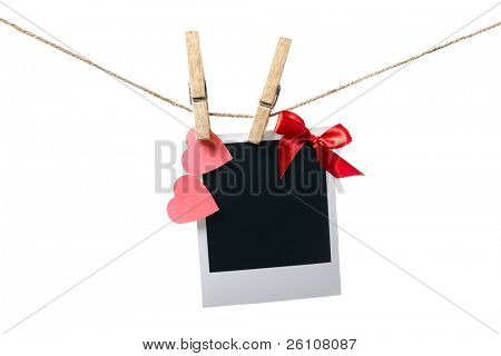 Blank instant photo with red bow and red paper hearts hanging on the clothesline. Isolated on white.