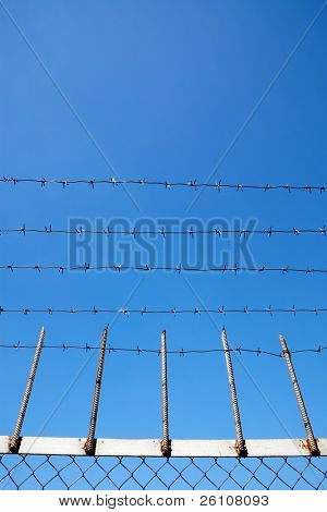 Barbed wire against clear blue sky. With part of metal fence.