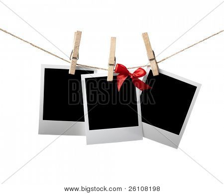 Blank instant photos with red bow hanging on the clothesline. Isolated on white.