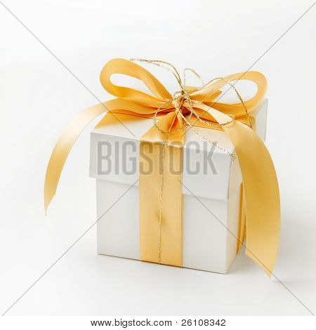 Single white gift box with gold ribbon on white background.