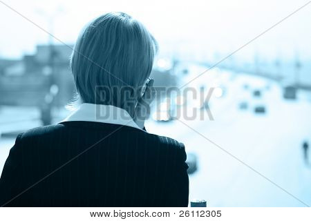 business woman speaks by phone in the street