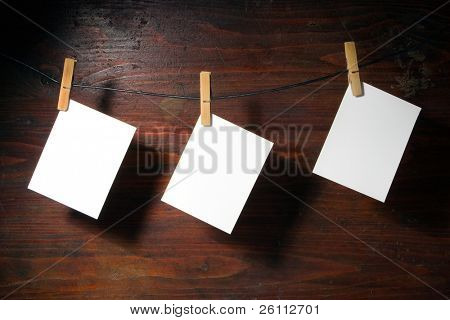 white   paper clothes-peg rope over grunge wood background