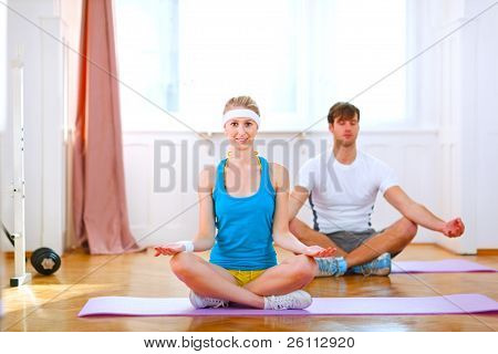 Healthy Couple Doing Yoga At Home