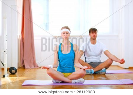Young Man And Fit Woman Doing Yoga At Home