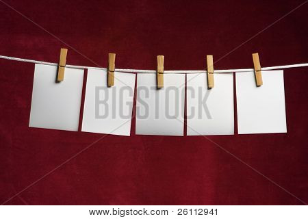 five white slip of paper attach to rope clothes peg on red