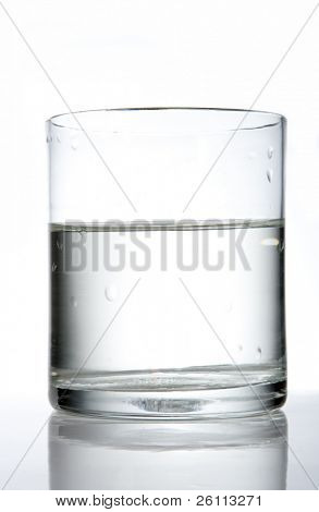 glass with water and reflection on white