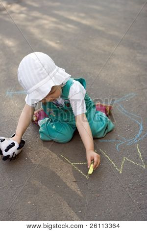 baby drawing chalk on asphalt lettesr ma