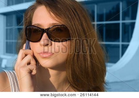 beauty sexy business woman with sunglass Speak cell phone on modern building