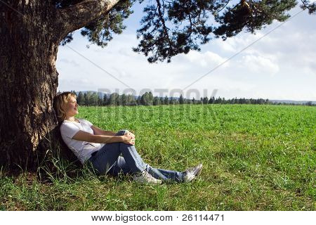 young beauty woman sit under alone tree in field under blue sky and clouds