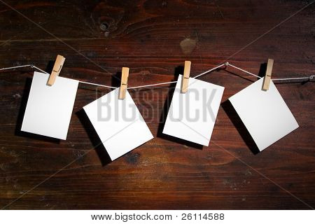 Photo paper attach to rope with clothes spins on wooden background