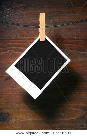palaroid blank clothes-peg rope over grunge wood background