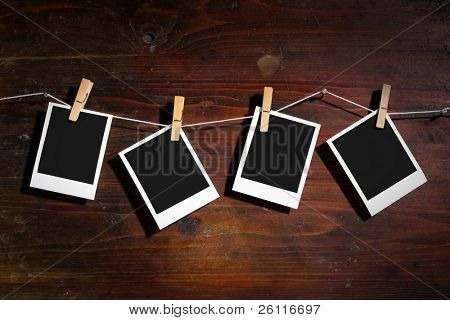 palaroid blank attach to rope with clothes spins on wooden background