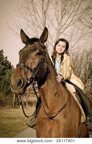 Young Woman Riding On Big Brown Horse