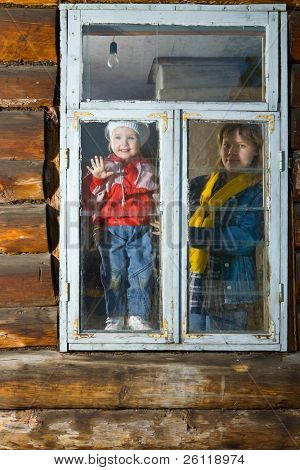 woman and child look in window in loghouse