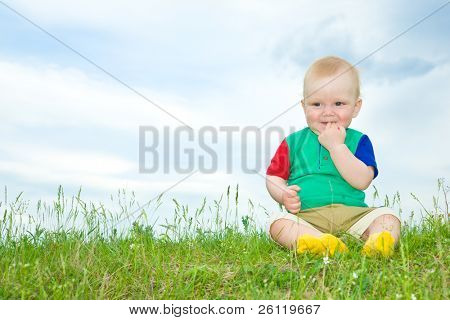 little baby sit on grass with hand in mouth under blue sky