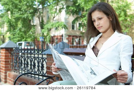 pretty business woman reading the newspaper
