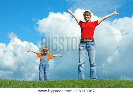 mother and child stand on green grass with open wide hand under sky with clouds