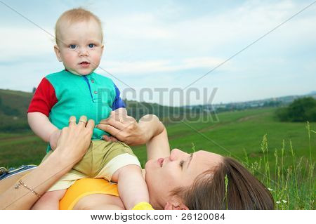 mother with baby on green grass under sky