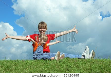 mother and baby on green grass under sky with clouds
