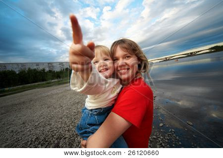 mother and child outdoor on stones and river