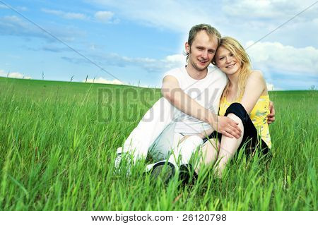 man and woman in green field under blue sky