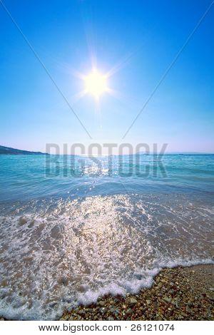sun in blue sky above sea