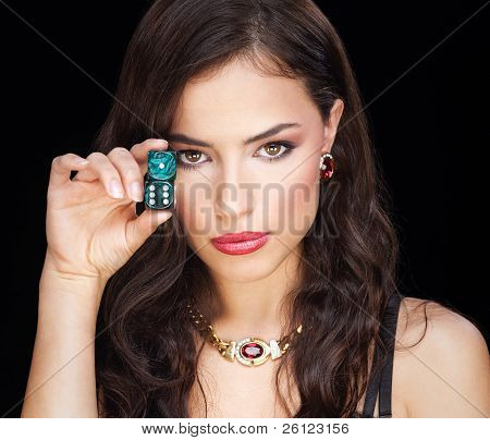 pretty woman holding dices on black background