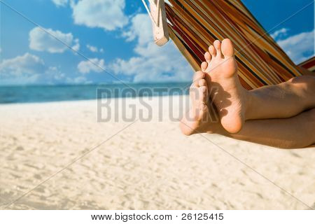 woman legs on hammock at sea beach