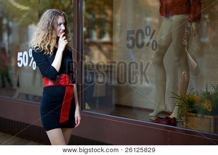 jovem mulher olhar nas montras com venda