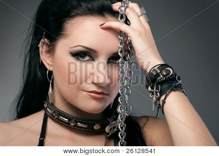 young naked woman in chain on black background