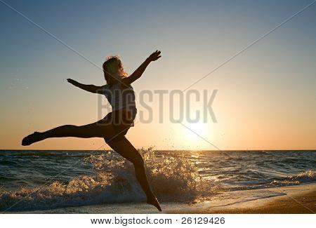 beauty woman run on sea beach on sunset