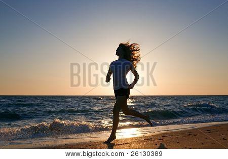 mujer de belleza ejecutar en la playa en puesta de sol