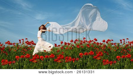 beauty woman in poppy field with white tissue under sky